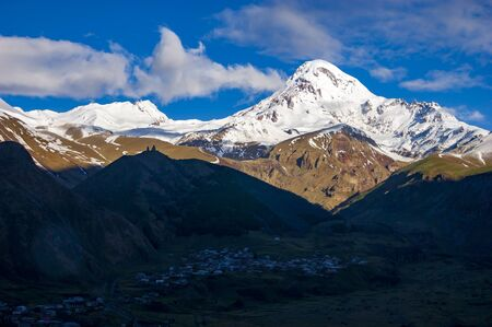 View of Kazbegi mountain and Stepantsminda village at sunrise Фото со стока