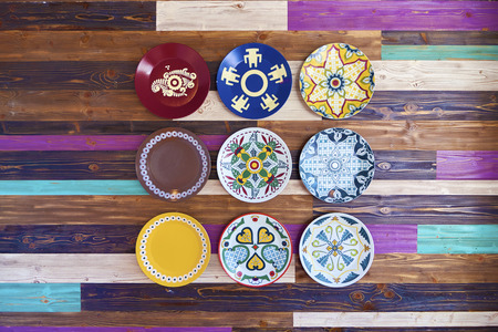 Grunge painted wooden wall with decorative colorful plates