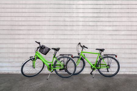 Green colored bicycles against concrete wall with stripes pattern Фото со стока