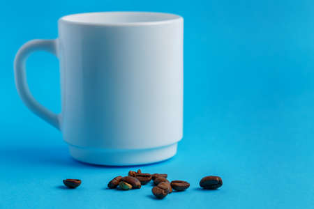 heap of coffee beans in front of a white washed cup on blue background