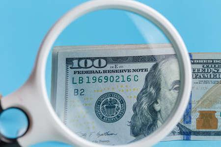 100 dollars through a magnifier closeup on a blue background 版權商用圖片
