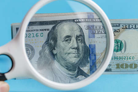 100 dollars through a magnifier close-up on a blue background