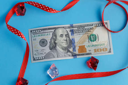 One hundred dollars banknote lies on a turquoise blue background next to a red pink pebbles and a red ribbon close up