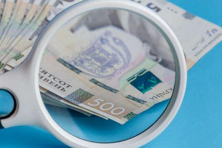 Deck 500 hryvnias deck through a magnifying glass closeup blue background 版權商用圖片