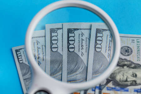 Deck of lying 100 dollars through a magnifier close-up on a blue background 版權商用圖片