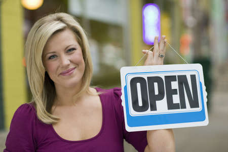 Pretty blond smiling woman holding up an open sign with urban background