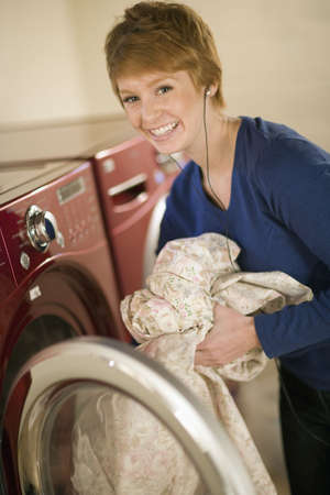 Smiling woman with earphones taking laundry out of dryer