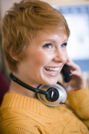 Young smiling woman talking on cell phone with headphones around her neck Stock Photo