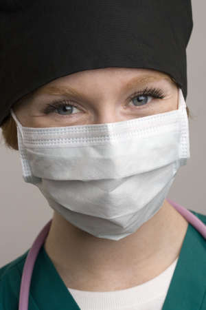 protective: Close up of smiling female medical staff wearing surgical mask