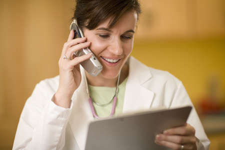 Woman doctor talking on cell phone and looking at a medical chart Stock Photo