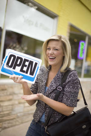 A happy owner holding up an Open sign in front of her new business photo