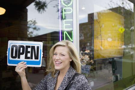 彼女の新しいビジネス前オープンの記号を持って幸せな所有者