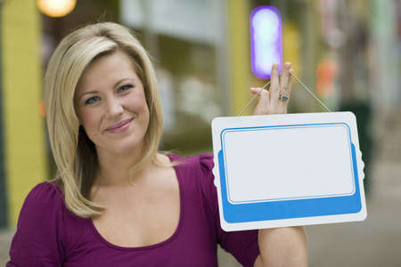 Pretty blond woman holding up a blank white sign with urban background photo