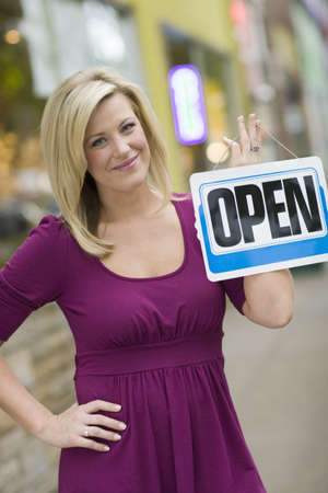 Pretty blond woman holding up an open sign with urban background