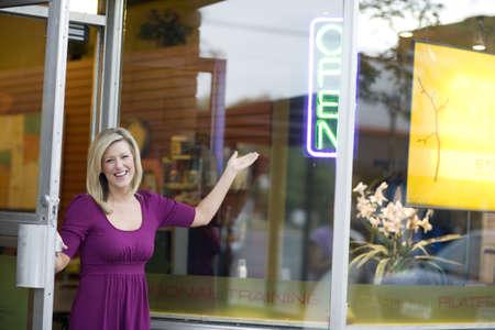 job opening: Un feliz propietario de apertura puerta de su tienda
