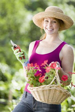 彼女の庭で若い女性切削花笑みを浮かべてください。 写真素材