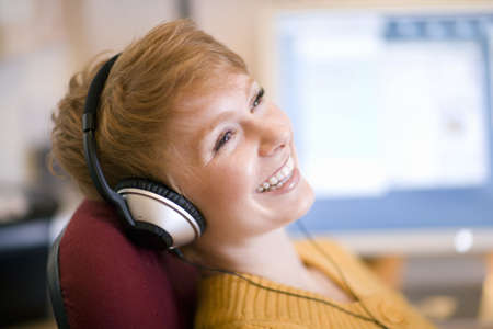 Young laughing woman relaxing in chair listening to headphones