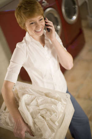 Smiling woman on cell phone holding laundry basket in laundry room