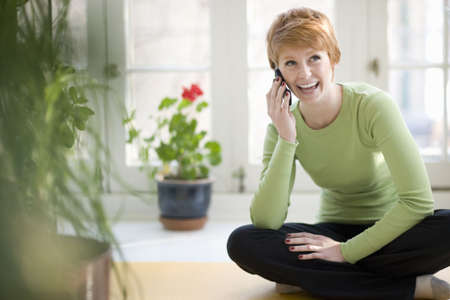 Happy young woman talking on a cell phone photo