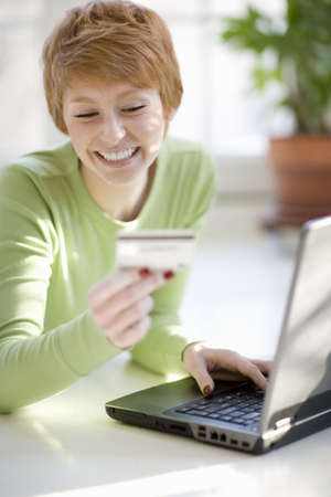 Smiling young woman shopping online with credit card and laptop computer photo