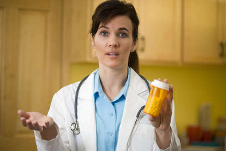 Woman doctor explaining prescription medication to the camera photo