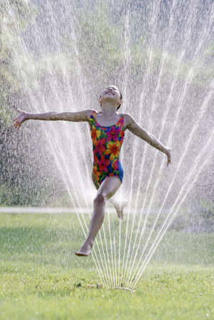Young girl with a joyful expression jumping through a spray of water