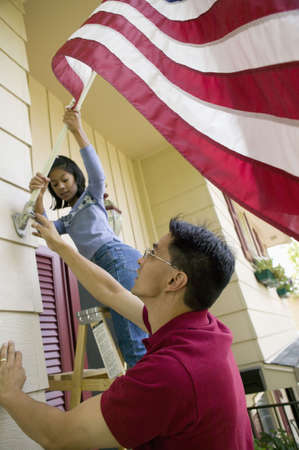 Father and daughter put a US flag on their house Stock Photo