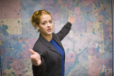 human geography: Young woman giving real estate presentation with map Stock Photo