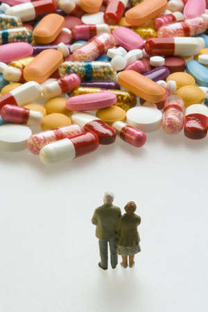 Miniature couple standing in front of capsules and pills Stock Photo