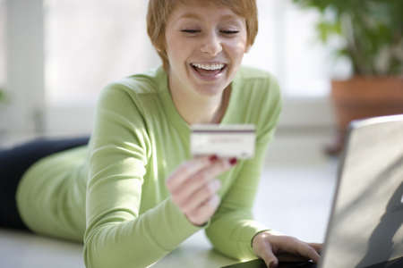 charge card: Smiling young woman shopping online with credit card and laptop computer
