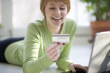 orden de compra: Sonriente mujer joven de compras en l�nea con tarjeta de cr�dito y computadora port�til