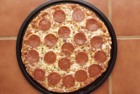 Delicious pepperoni and cheese pizza in a pan on the kitchen countertop Stock Photo - 2418969