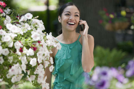 A young woman smiles while talking on her cell phone in a garden. Horizontal format. Stock Photo