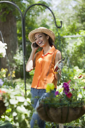 A smiling young woman chats on a cellphone while taking a break from gardening. Vertical format.