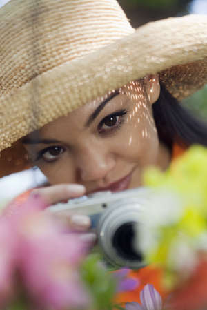 Close-up of a young woman in a sun hat, taking pictures of flowers. Vertical format.