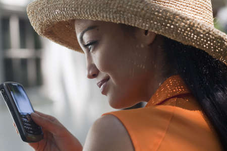 Close-up side view of a young woman wearing a sun hat and texting on her cell phone. Horizontal format.