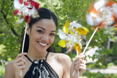 Close-up of a happy young woman outdoors, holding three pinwheels.  Horizontal format.