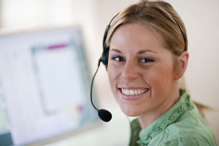 Close-up of a young woman in front of a computer, wearing a headset and smiling at the camera. Horizontal format. photo