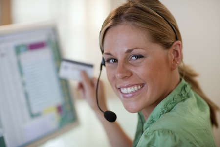 Close-up of a smiling young woman in front of a computer, wearing a headset and holding a credit card. Horizontal format.