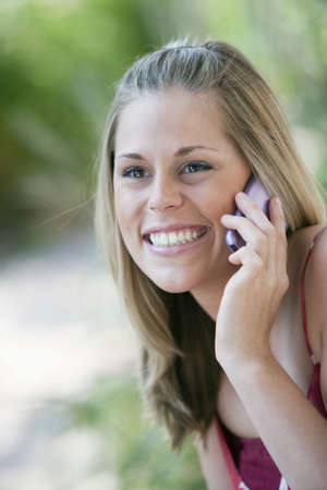 Close-up of a smiling young woman using a cell phone in an outdoor setting. Vertical format. photo