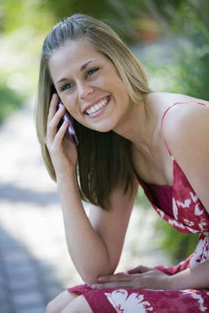 Smiling young woman talking on a cell phone in an outdoor setting. Vertical format. photo