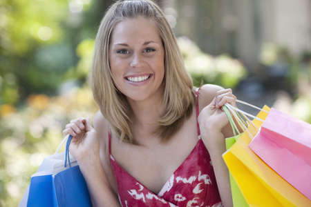Young woman holding shopping bags and smiling at the camera. Horizontal format. Stock Photo