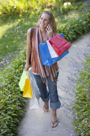 High angle view of a woman holding shopping bags and using a cell phone. Vertical format. photo