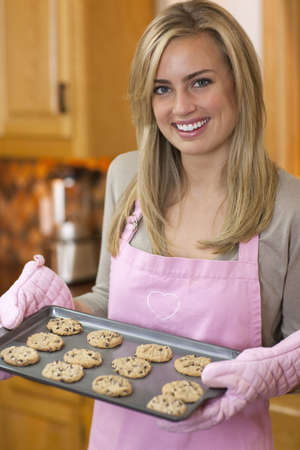 A young woman is holding a baking sheet of cookies and smiling at the camera.  Vertically framed shot.
