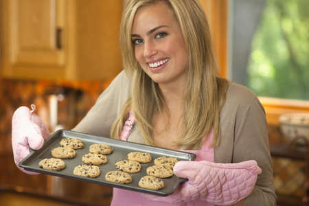 A young woman is holding a baking sheet of cookies and smiling at the camera.  Horizontally framed shot.