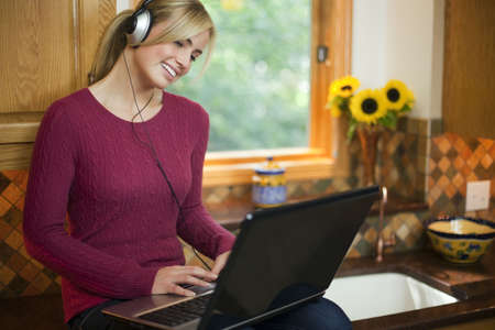 A young woman is working on a laptop in her kitchen.  She is wearing headphones, smiling, and looking away from the camera.  Horizontal.
