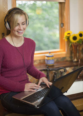 A young woman is working on a laptop in her kitchen.  She is wearing headphones, smiling, and looking away from the camera.  Vertical.