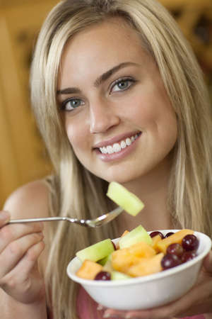 A young woman is holding a bowl of fruit and smiling at the camera.  Vertically framed shot. Stock Photo