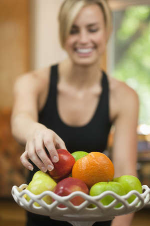 A young woman is picking up a piece of fruit, smiling, and looking away from the camera.  Vertically framed shot. Stock Photo - 5999888