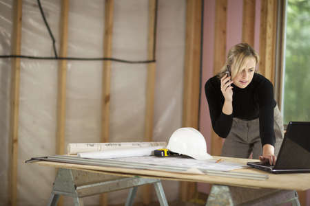 A young woman is looking at a laptop and talking on the phone.  She is working at a construction site.  Horizontally framed shot.